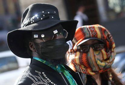 Una pareja luce máscaras sanitarias faciales para protegerse del coronavirus, en un desfile de Dolce & Gabbana.