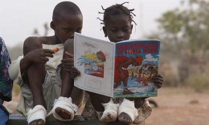 Fatawu Yakubu (izquierda) y Sadia Mesuna leen un cómic sobre el gusano de Guinea en un centro de pacientes en Ghana, en 2007.