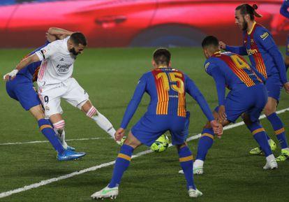 El delantero francés del Real Madrid Karim Benzema intenta un lanzamiento ante varios rivales del Barcelona.