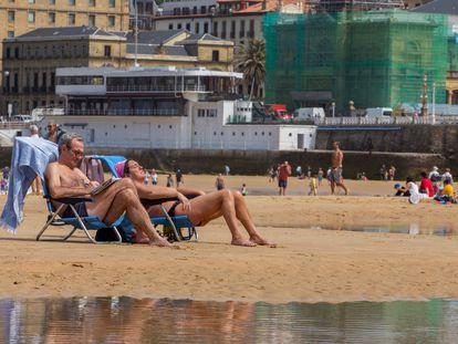 Varias personas disfrutan el lunes de la playa en San Sebastián.