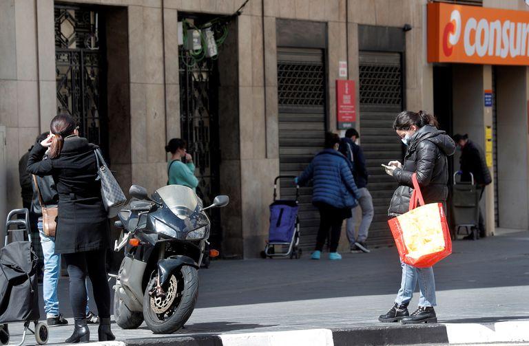 Varias personas guardan cola para realizar la compra en un supermercado en Valencia.