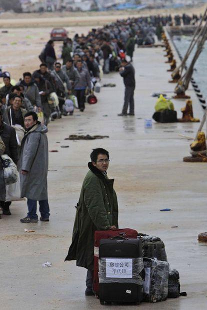 Ciudadanos de varias nacionalidades esperan un barco en el puerto de Bengasi.