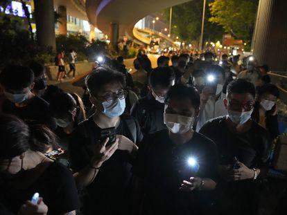 Varios hongkoneses encienden velas y las luces de sus móviles para recordar la matanza de Tiananmén, este viernes fuera del parque Victoria de Hong Kong.