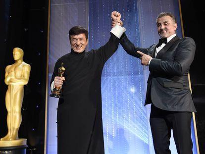 Jackie Chan recibe con el Oscar en la mano la felicitación de Sylvester Stallone.