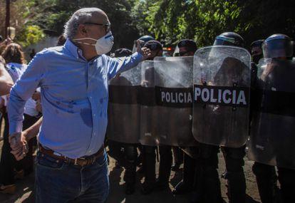 El periodista Carlos Fernando Chamorro, director de 'Confidencial', le reclama a la policía frente a las oficinas de su revista en Managua, el 14 de diciembre de 2020.