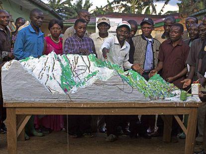 El maestro pigmeo Irangi (en el centro) muestra un mapa tridimensional de su zona en la Reserva de Itombwe, en RDC.