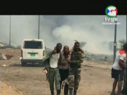 Imagen de la televisión pública de Guinea Ecuatorial en la que dos soldados asisten a un herido tras la explosión de un arsenal de armas en un cuartel de Bata este 7 de marzo.