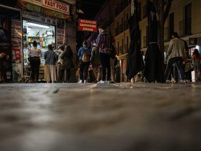Jóvenes hacen cola para comprar en una tienda de Madrid, en la madrugada del 9 de mayo, tras acabar el estado de alarma.