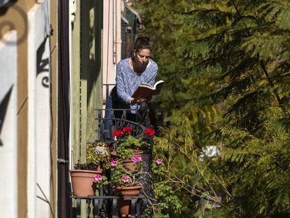 Una mujer lee en un balcón de Barcelona durante el confinamiento por el nuevo coronavirus.
