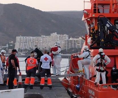 Miembros de la Cruz Roja ayudan a bajar del barco a migrantes en el puerto de Arguineguín (Gran Canaria, España) a 17 de marzo de 2021. 79 inmigrantes de origen subsahariano que viajaban a bordo de dos pateras fueron trasladados esa tarde noche por Salvamento Marítimo hasta el muelle de Arguineguín, en el Sur de Gran Canaria,  después de rescatarlos en alta mar. Entre ellos viajaban varios bebés, mujeres jóvenes y adultos.