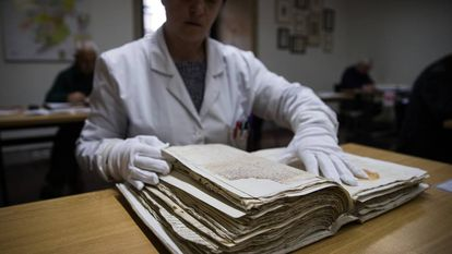 Una trabajadora del Archivo Histórico Diocesano de Santiago consulta datos en un manuscrito.