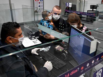 Viajeros con mascarillas en el aeropuerto de Bogotá. En vídeo, el anuncio del cierre de fronteras de los tres países.
