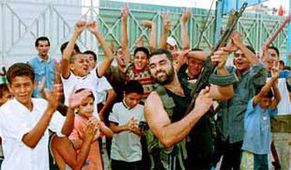 Un palestino dispara su rifle en señal de alegría en un campo de refugiados en Sidón, al sur del Líbano.