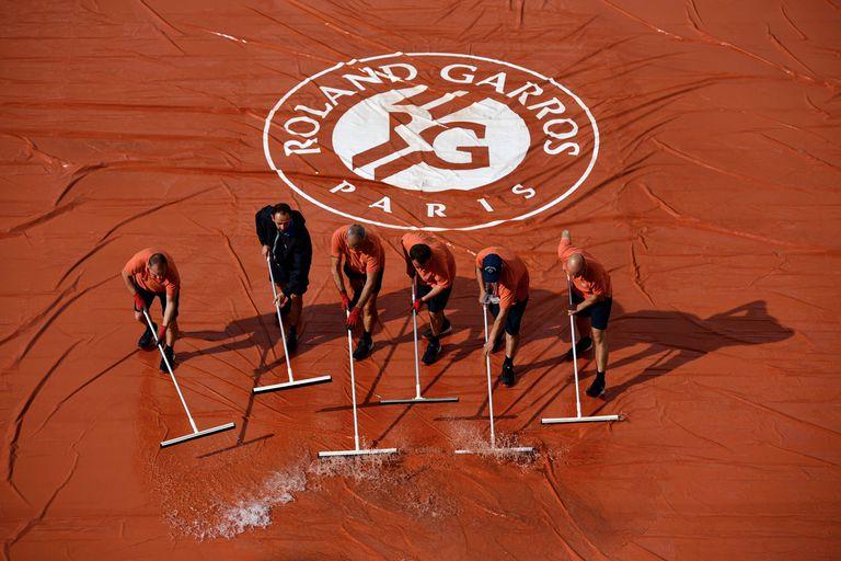 Empleados de pista retiran agua de la pista central en la última edición de Roland Garros.