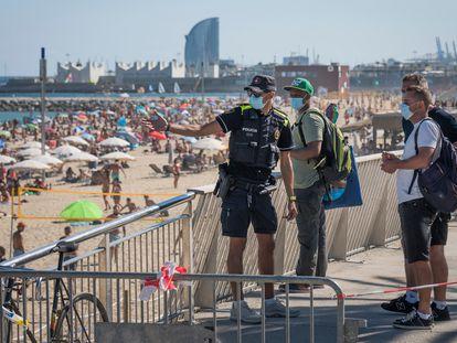 Varias personas intentan acceder a la playa de Bogatell (Barcelona) el domingo a pesar de la prohibición.