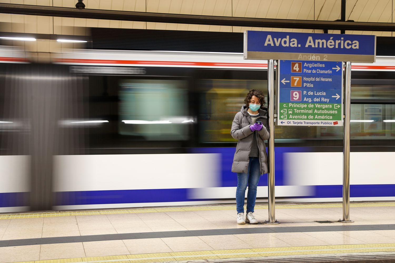 Pasajera del metro consultando su teléfono en a estación de Avenida de América.