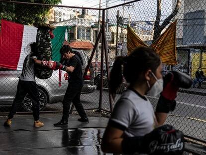 Una niña y dos jóvenes entrenan boxeo en una escuela ubicada en un bajopuente en Azcapotzalco, Ciudad de México, el 9 de septiembre de 2021.
