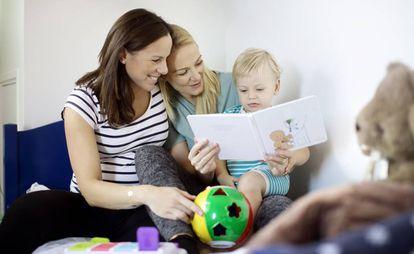 Dos madres leen un cuento a su hijo.