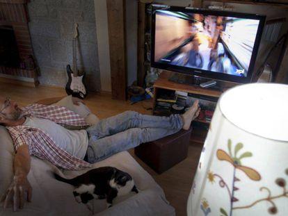 Un espectador dormido frente a la pantalla de televisión durante la emisión de un programa de máxima audiencia.