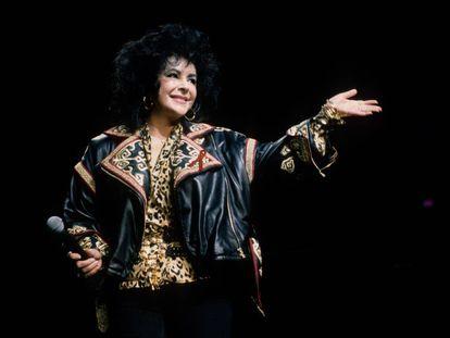 Elizabeth Taylor, gran defensora de la lucha contra el sida, saluda en el escenario en un concierto de Elton John celebrado en 1992.