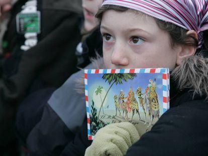 Un niña sostiene una carta para los Reyes Magos, en la tradicional cabalgata de los Reyes Magos de Barcelona.