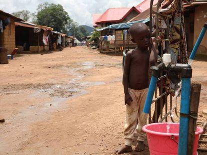 Un niño permanece junto a una bomba de agua instalada por una empresa minera china en Masumbiri, Sierra Leona, el 26 de julio de 2019.