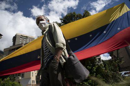 Una persona con una máscara protectora camina hacia un centro de votación durante un plebiscito liderado por la oposición en el barrio Terrazas del Ávila de Caracas, Venezuela, el sábado 12 de diciembre de 2020.