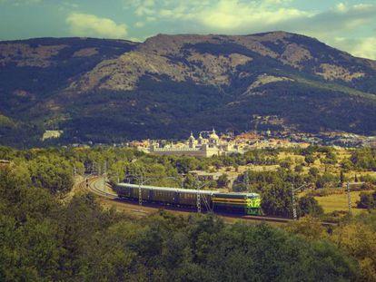 El tren turístico de Felipe II y, al fondo, el Real Sitio de San Lorenzo de El Escorial.