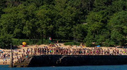 Grupos de jóvenes hacen cola para saltar al mar en el espigón de la playa de la Magdalena de Santander este lunes.