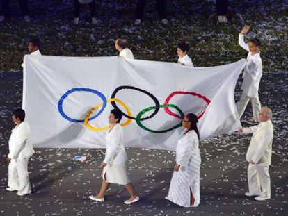 Silva saluda mientras porta la bandera olímpica junto a otras personalidades.