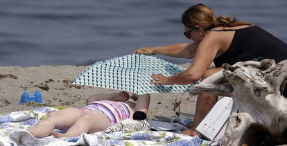 Una madre coloca un paraguas para proteger a su hija del calor.