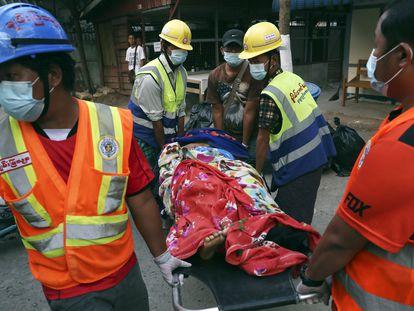 Miembros de un equipo voluntario de rescate transportan a una mujer herida en las protestas, este domingo en la ciudad de Mandalay (Myanmar).