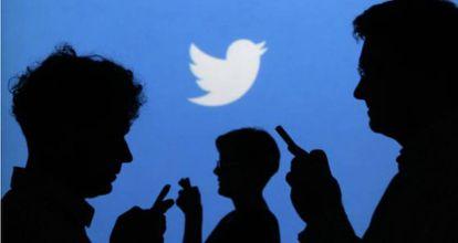 Personas que usan sus móviles frente a un cartel de Twitter