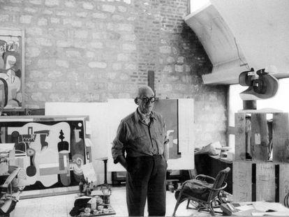 Le Corbusier en su estudio que estaba separado de la zona de vivienda por una puerta doble de una sola hoja que hacía también las veces de armario.