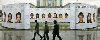 Varias personas pasan ante un cartel promocional de Alemania y Europa  colocado delante de la Cancillería ayer en Berlín.