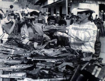 Carlos Pizarro, líder del M-19, envuelve su pistola en una bandera colombiana en el acto de entrega de armas del grupo guerrillero, en marzo de 1990.