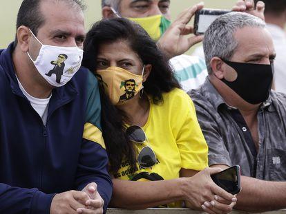 Seguidores de Bolsonaro con mascarillas de Bolsonaro esperan este lunes al presidente ante su residencia, en Brasilia.