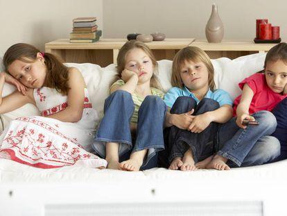 Cuatro niños se aburren en el sillón.