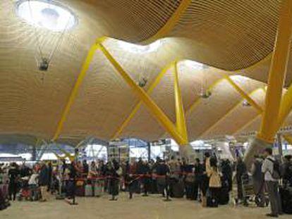 Numerosas personas esperan en los mostradores de facturación de la Terminal 4 (T4) del aeropuerto de Barajas. EFE/Archivo