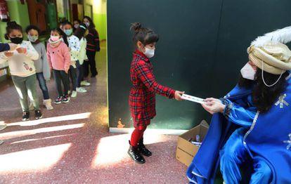 Una niña entrega su carta al paje de los Reyes Magos el último día de clase en en el colegio El Valles de Terrasa.