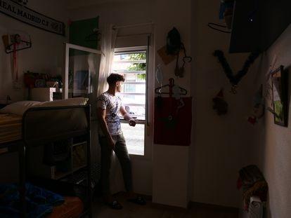 Omar Kordala mira por la ventana de su habitación en el piso tutelado donde vive en el barrio de Usera en Madrid, en julio de 2021.