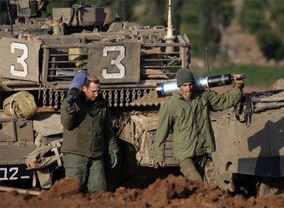Soldados israelíes acarrean proyectiles en el lado israelí de la frontera con Gaza.