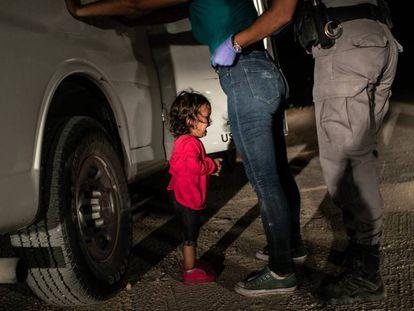 La niña Yana, de Honduras, llora mientras su madre, Sandra Sánchez, es cacheada por un policía estadounidense de fronteras en McAllen (Texas).
