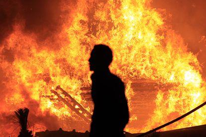 Un opositor al régimen de Mubarak camina pasa frente al fuego en una calle del centro de El Cairo