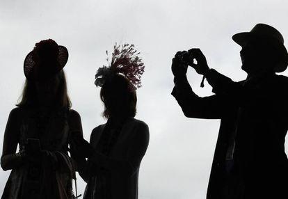 Un hombre toma una foto de dos mujeres, en una carrera de caballos en Kentucky, el pasado 3 de mayo.
