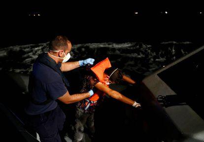 Un migrante tunecino es ayudado por un oficial maltés.