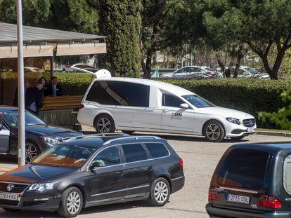Empleados de la funeraria municipal introducen el féretro de un muerto por coronavirus en un coche, en el tanatorio Sur de Madrid.