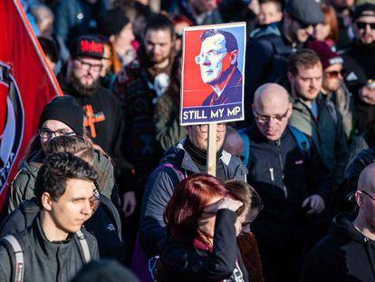 Un manifestante con una imagen del líder de La Izquierda Bodo Ramelow, en una marcha de protesta en Erfurt, capital de Turingia, el pasado sábado.