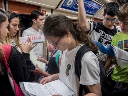 Algunos estudiantes repasan en el trayecto en metro hasta Ciudad Universitaria de Madrid durante la EBAU 2019.