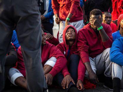 Un grupo de inmigrantes custodiado por la Policía Nacional, en el puerto de Algeciras en 2018. En vídeo, declaraciones de Patricia Bárcenas, presidenta de CEAR.